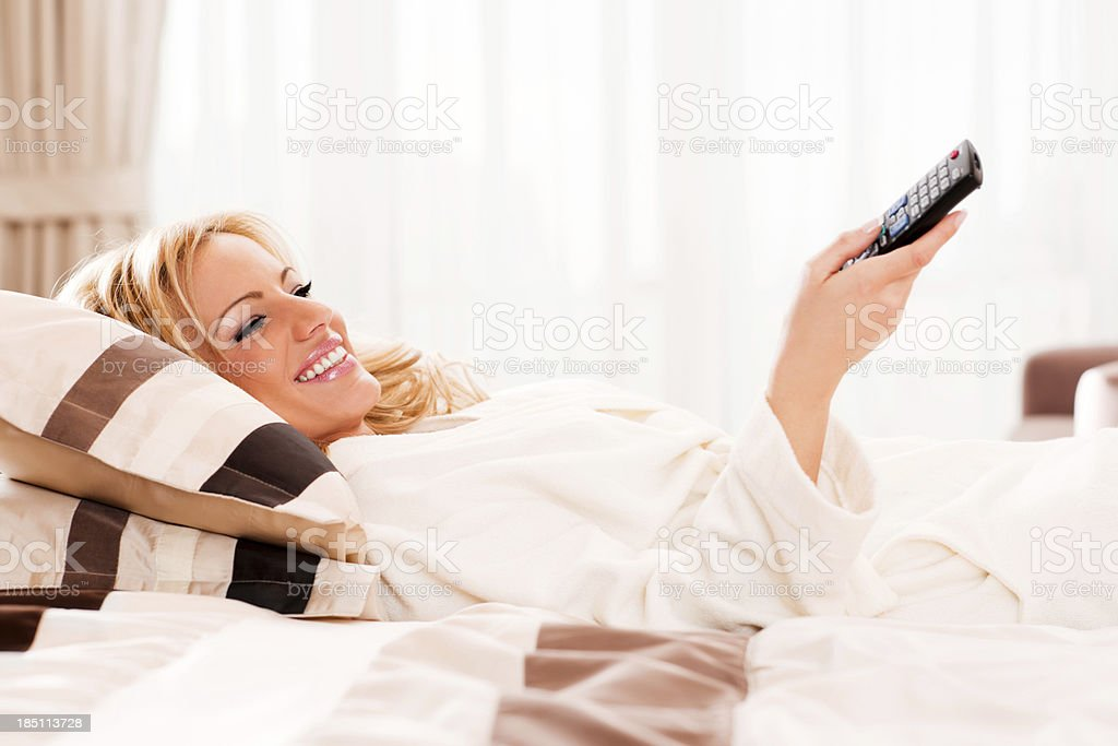 Cheerful blonde woman lying on the bed in her bathrobe and watching...