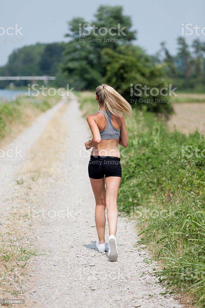 Beautiful blonde woman running along the riverside royalty-free stock photo
