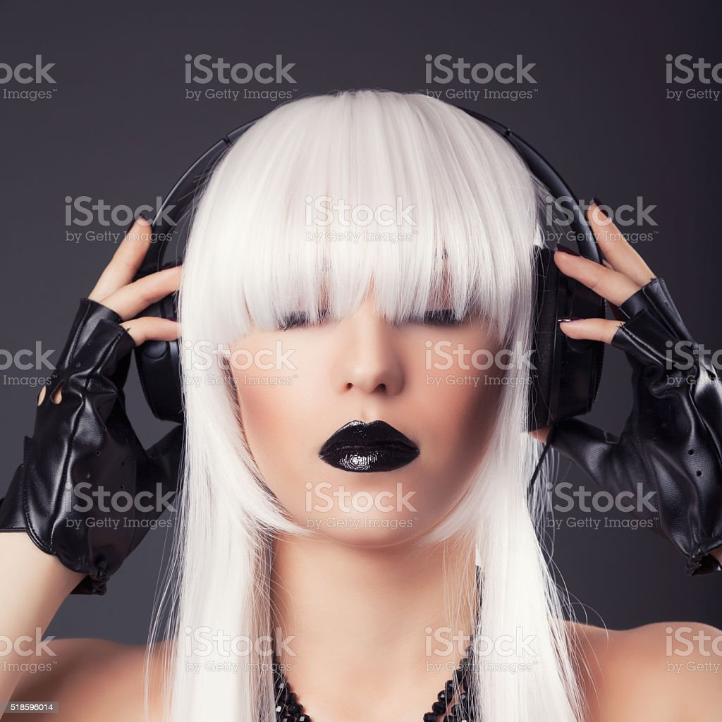 beautiful blonde woman with black make-up and accessories listen stock photo