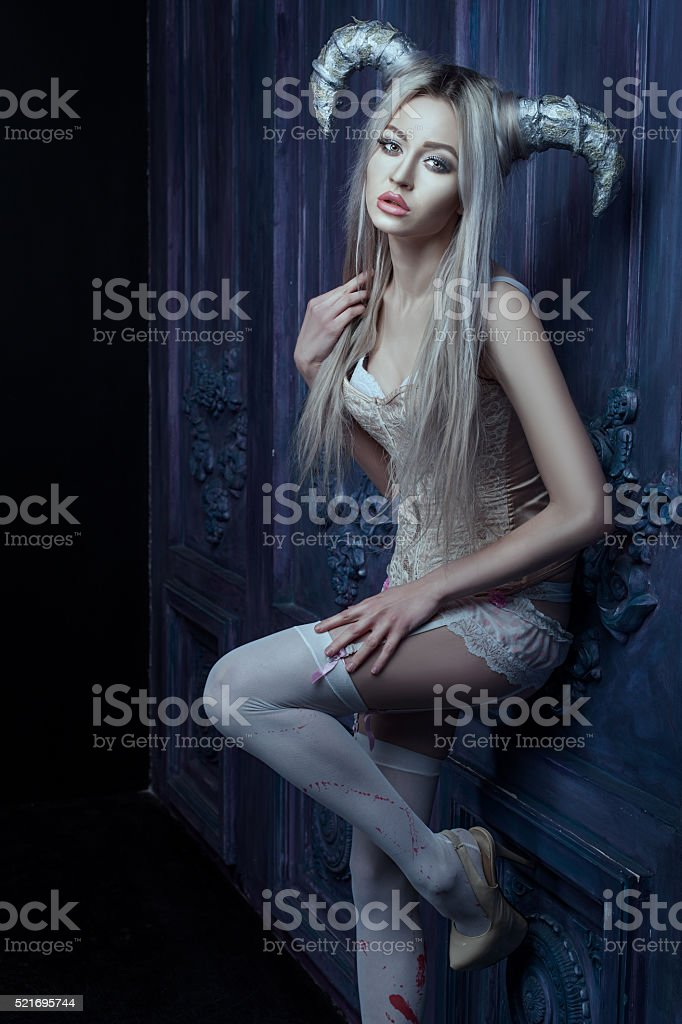 Beautiful blonde woman with horns. stock photo