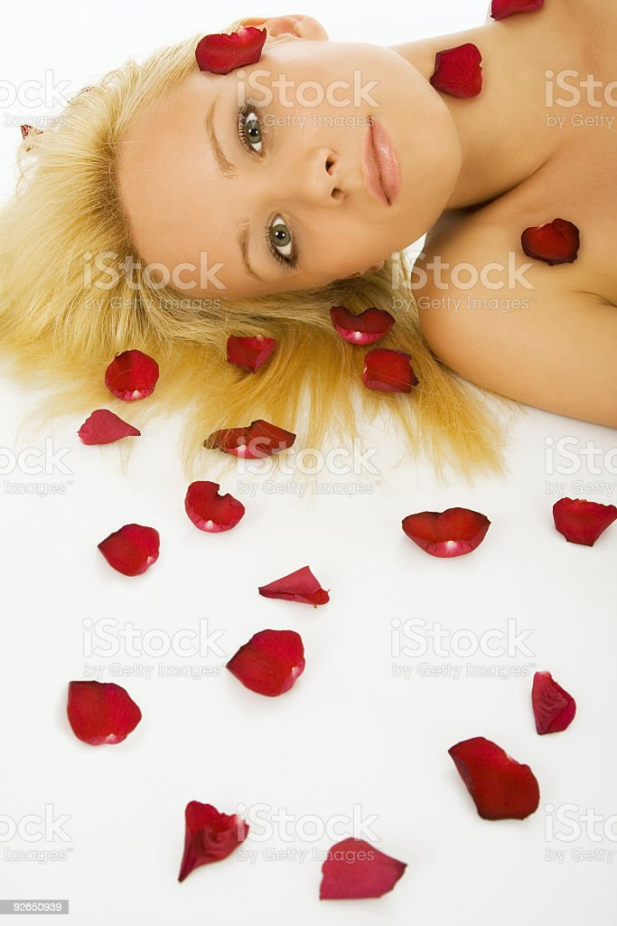 Beautiful blonde woman with lot of red rose petals stock photo