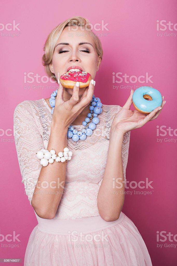 Beautiful blonde women eating colorful dessert. Fashion shot. Soft colors stock photo