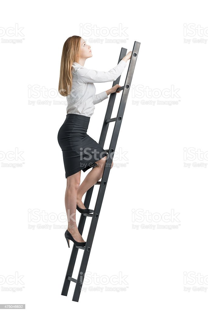 Beautiful blonde young woman is climbing up on the ladder stock photo