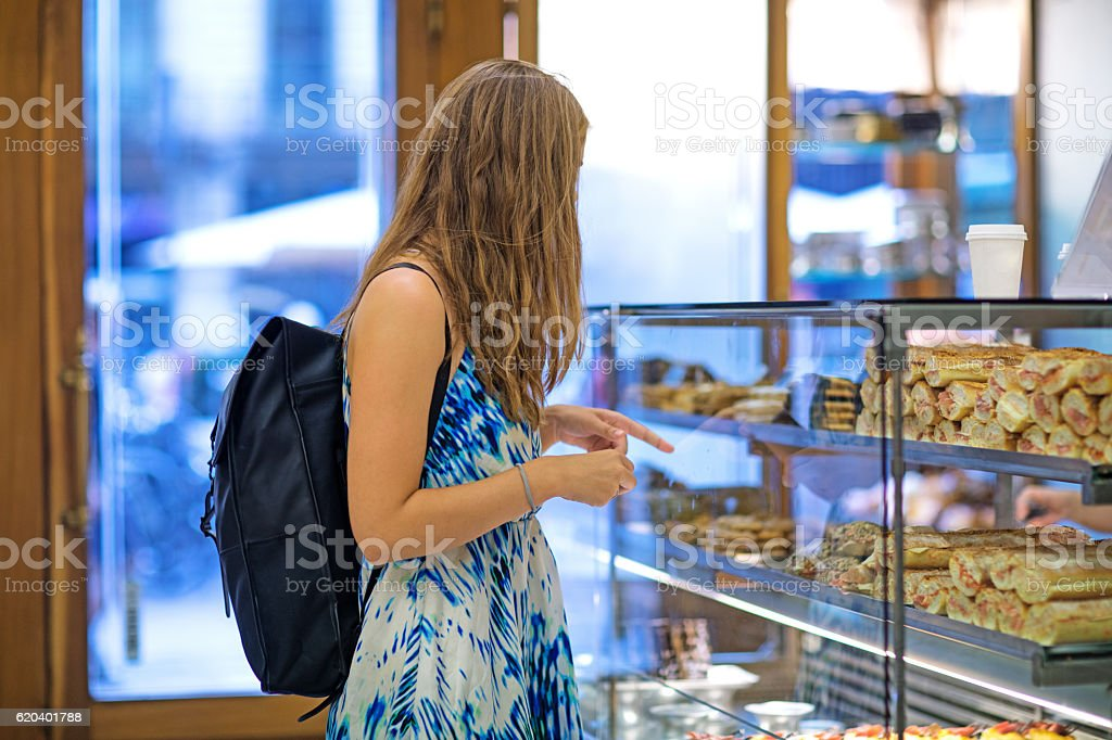 Beautiful blonde young woman student shopping in daytime european bakery stock photo