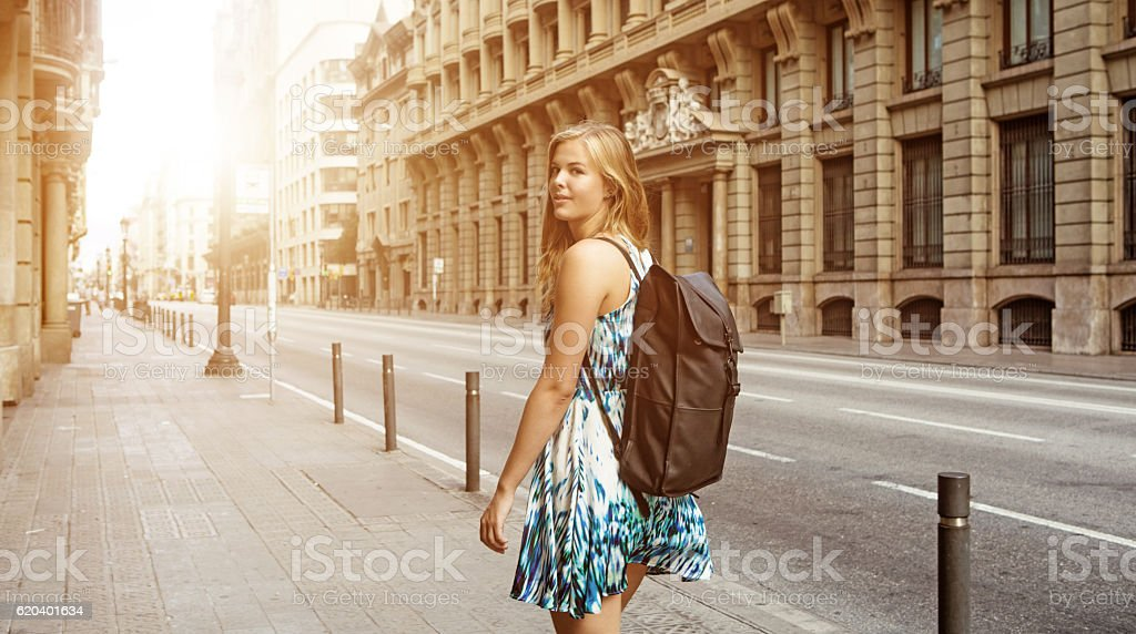 Beautiful blonde young woman student walking in daytime european city stock photo