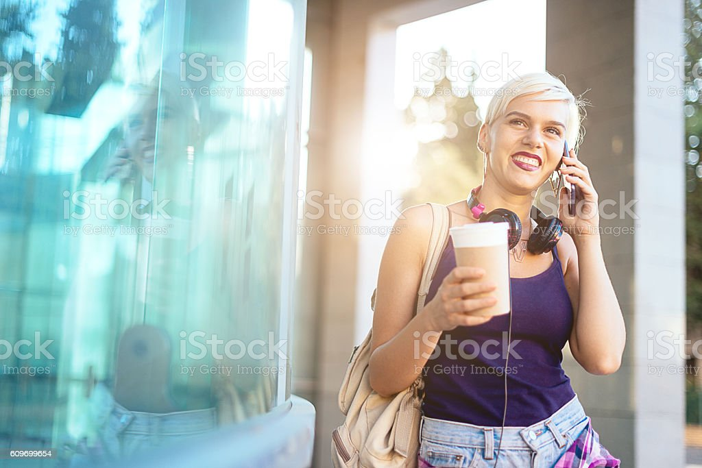 Beautiful blonde young woman talking on smartphone stock photo