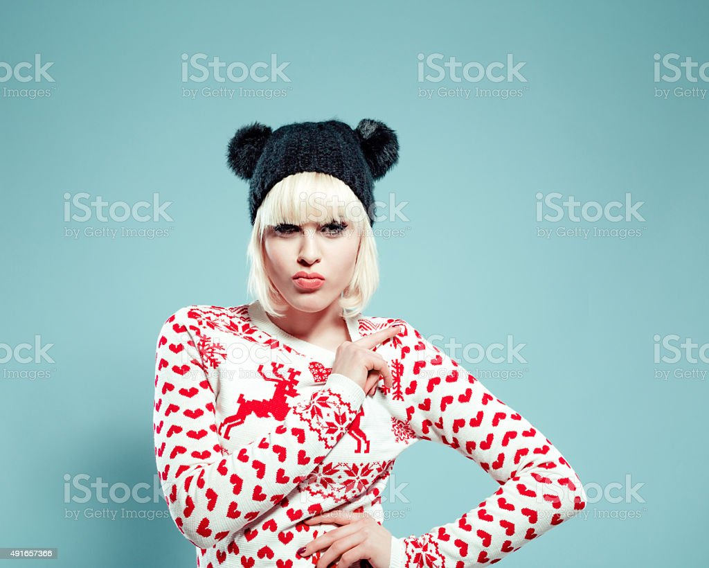 Beautiful blonde young woman wearing xmas sweater and bobble hat stock photo