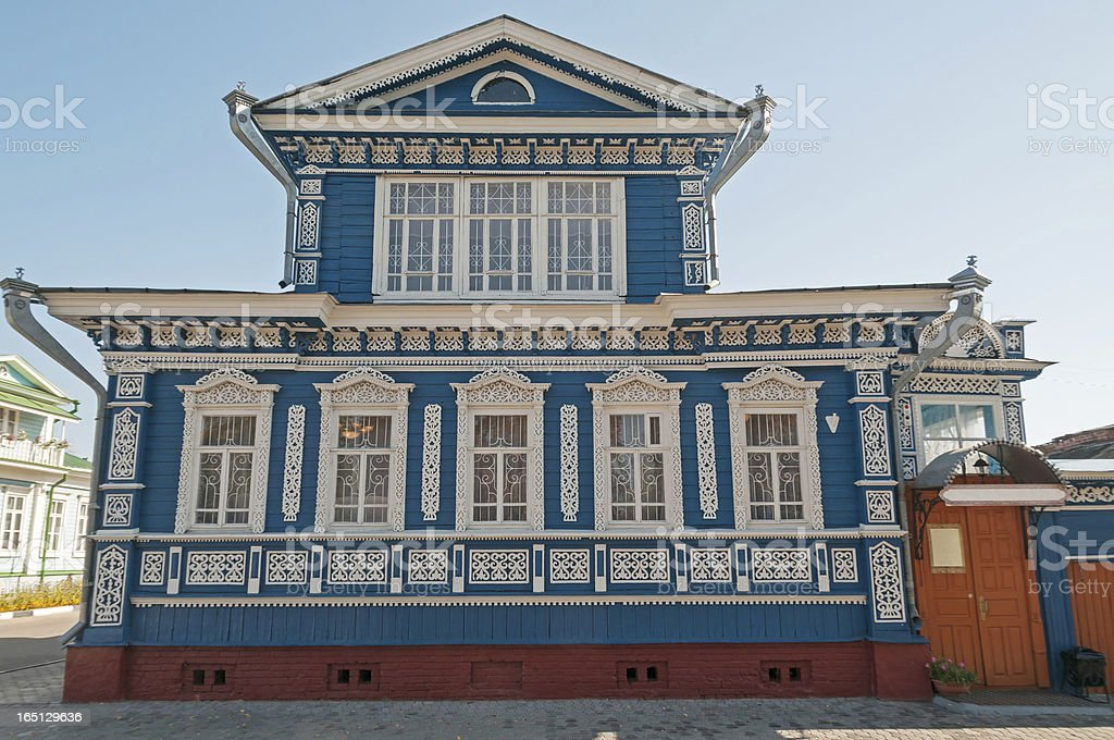 Beautiful blue wooden house with fretted white window cases royalty-free stock photo
