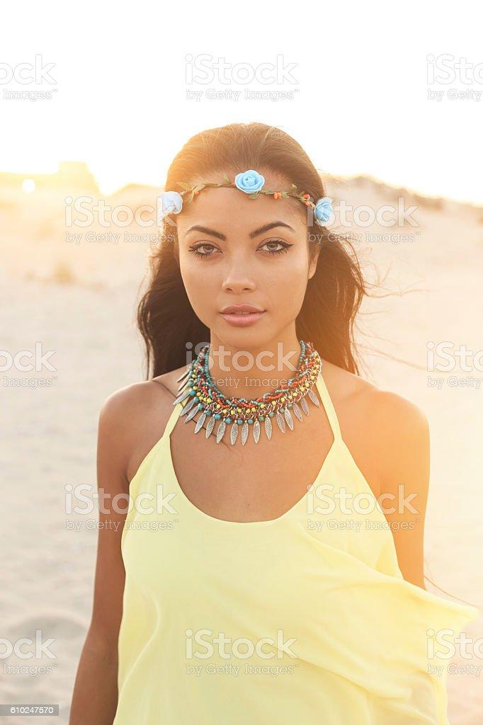 Beautiful boho asian woman with wreath walking on beach stock photo