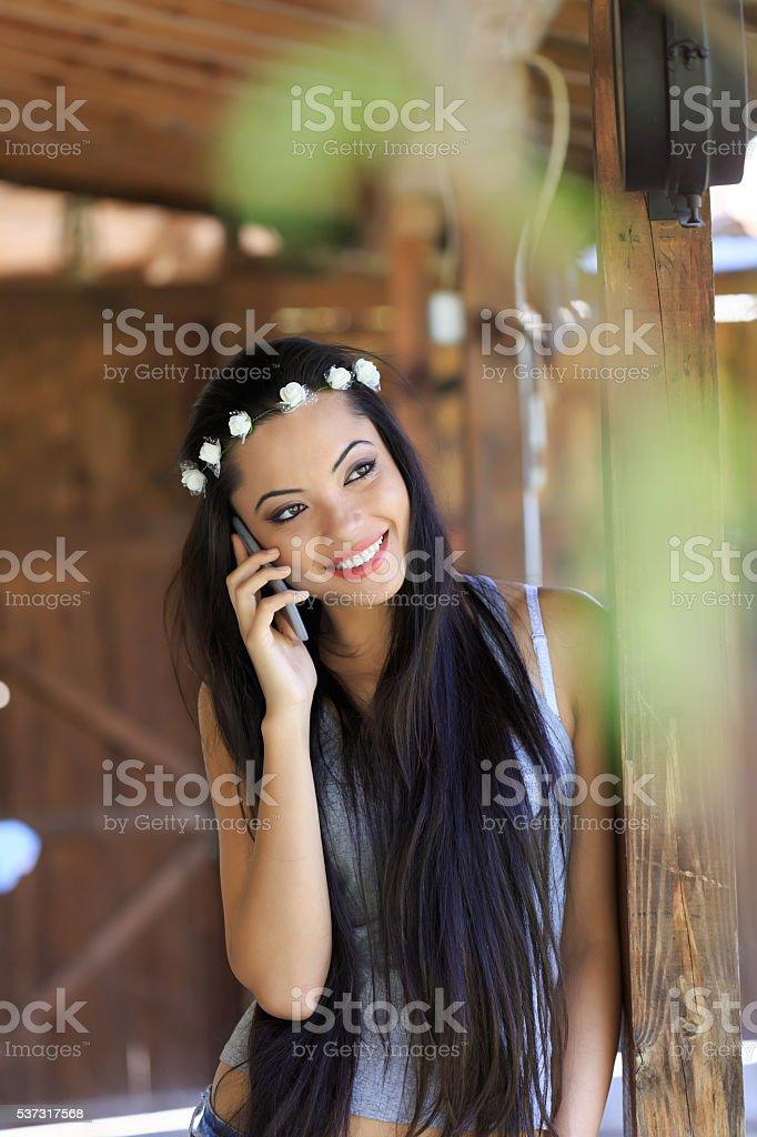 Beautiful boho woman with wreath talking on the phone stock photo