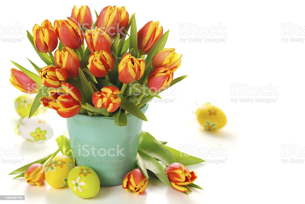 Beautiful bouquet of tulips in vase with Easter eggs. stock photo