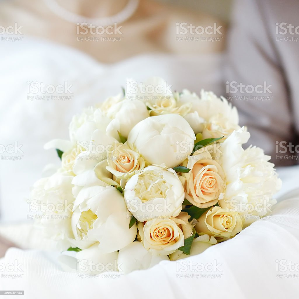 A beautiful bouquet of white flowers on a white dress stock photo