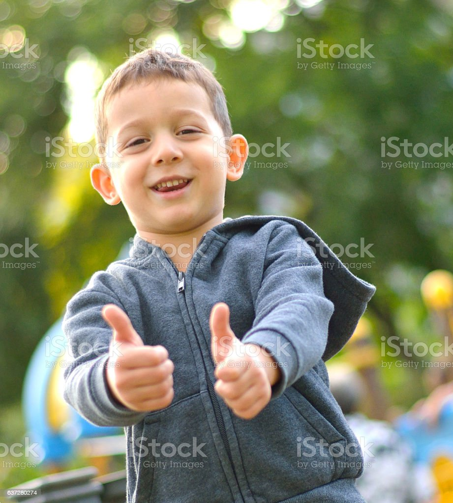 Beautiful Boy in Playground Showing Tumbs Up stock photo