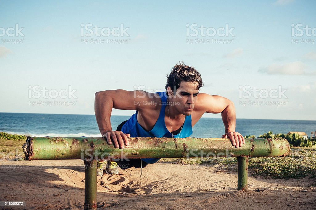 beautiful brazilian musculated man doing push-ups at beach stock photo