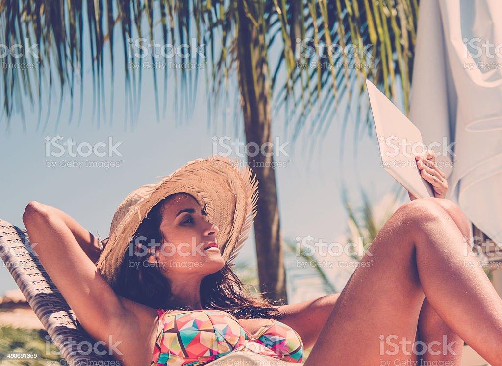 beautiful brazilian woman in sun chair holding digital tablet stock photo