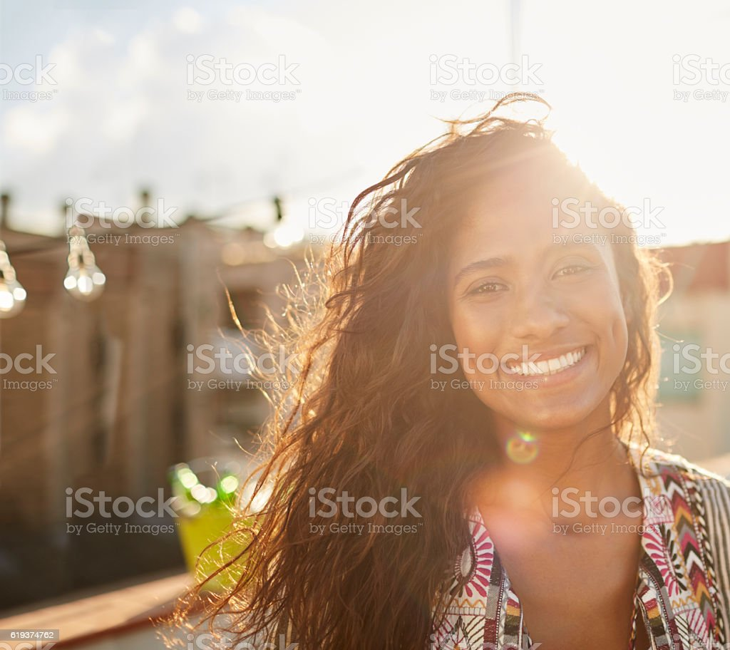 Beautiful Brazilian woman looking at camera with sunflare. stock photo