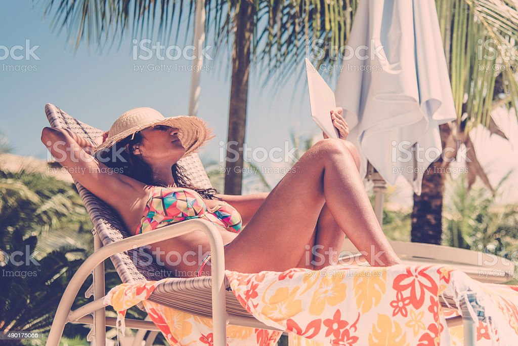 beautiful brazilian woman with digital tablet in tropic sun stock photo