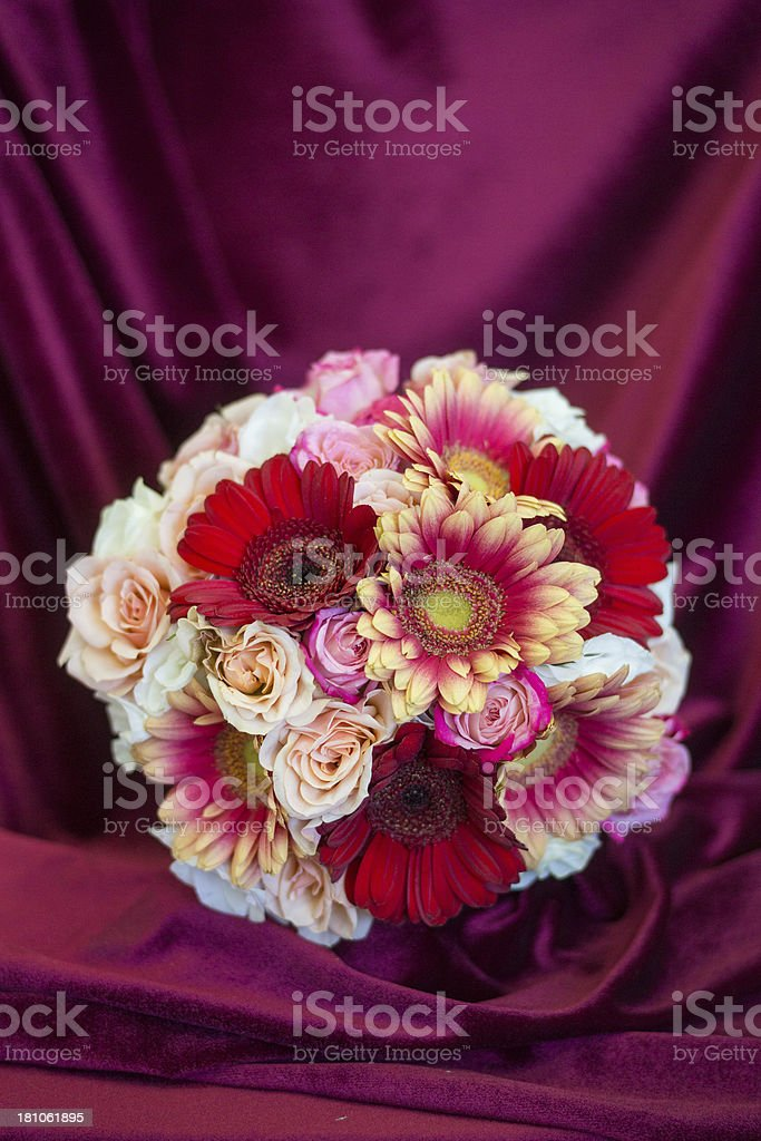 Beautiful bridal bouquet on dark red textile background royalty-free stock photo