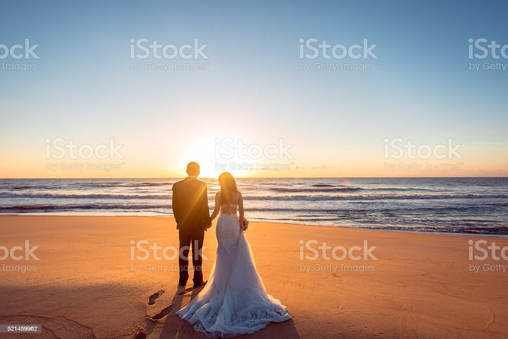 Beautiful bride and groom at the beach stock photo