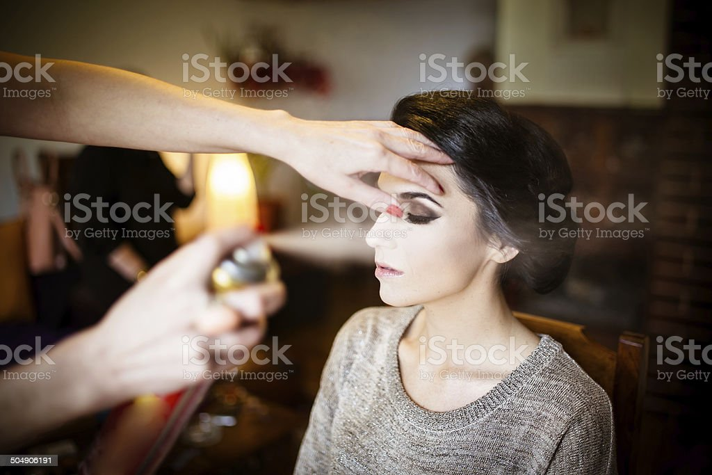 Beautiful bride doing her hair and makeup stock photo