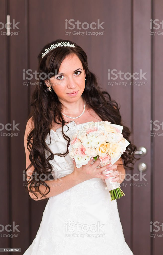 Beautiful bride girl in wedding dress with bouquet of flowers stock photo