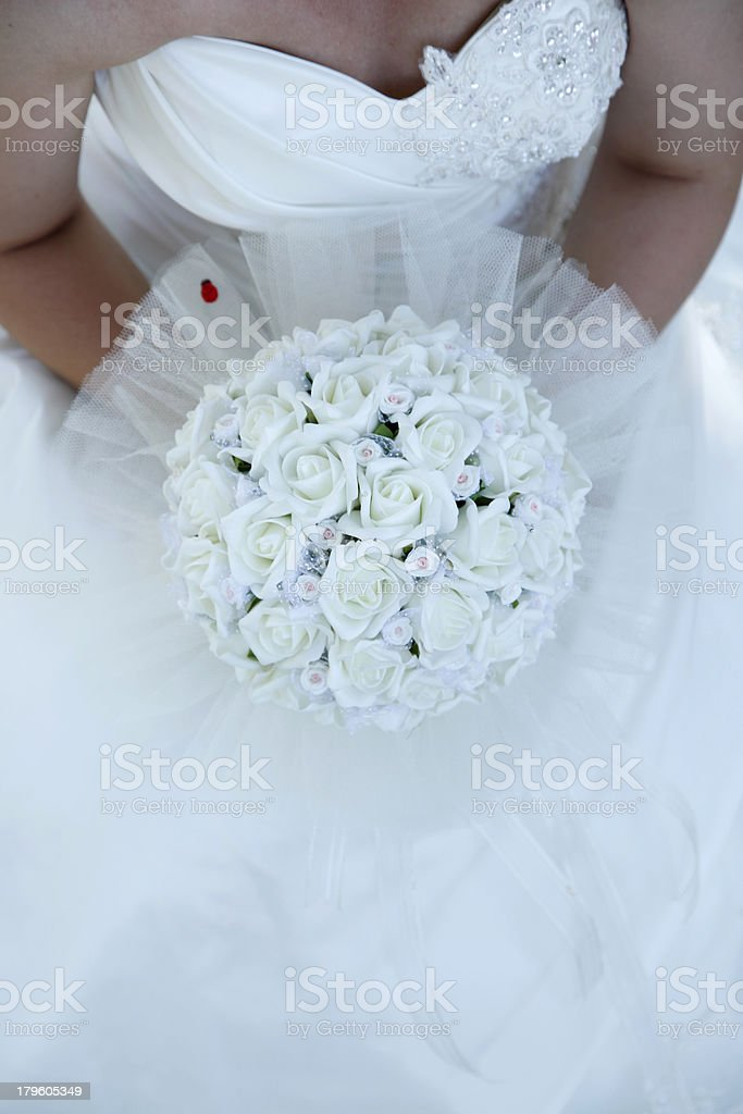 Beautiful bride holding a bouquet of white flowers royalty-free stock photo