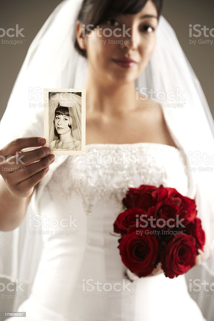 Beautiful Bride Holding up a Vintage Photograph. royalty-free stock photo