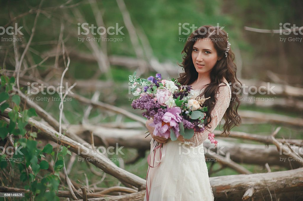 Beautiful bride in the forest with a large bouquet of stock photo