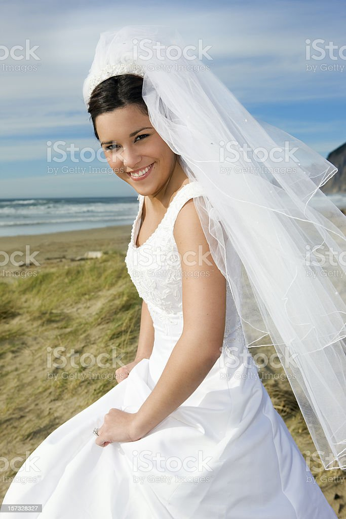 Beautiful Bride in Wedding Gown on Beach, Smiling at Camera royalty-free stock photo