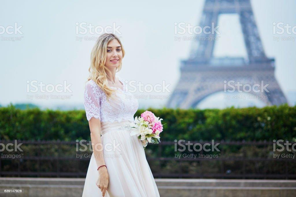 Beautiful bride in white dress near the Eiffel tower stock photo