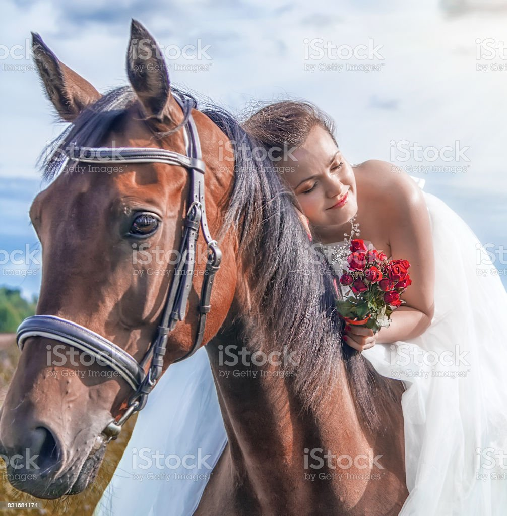 Beautiful  bride, lying on a horse on her wedding day stock photo
