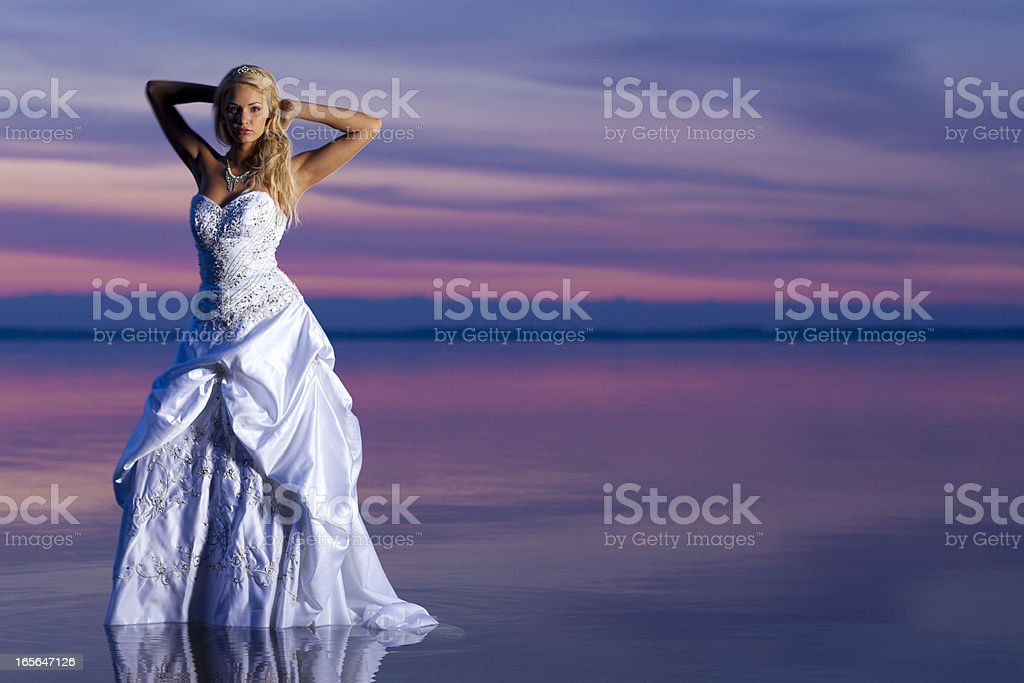 Beautiful bride on lake in the sunset stock photo