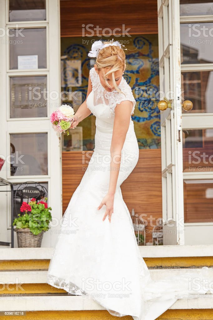 Beautiful Bride on Staircase with Dress Hiked Up. stock photo