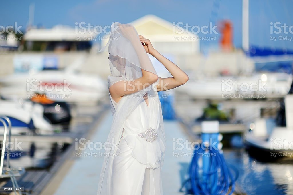 Beautiful bride posing in a harbor stock photo