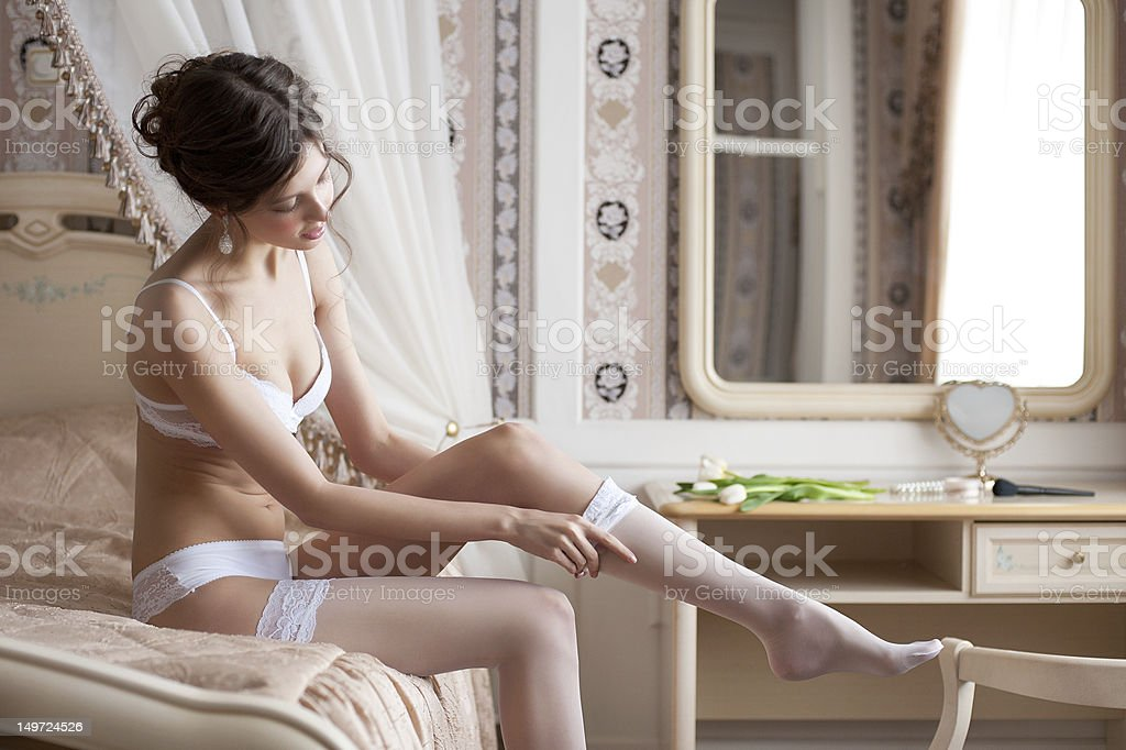 Beautiful bride putting on stockings royalty-free stock photo