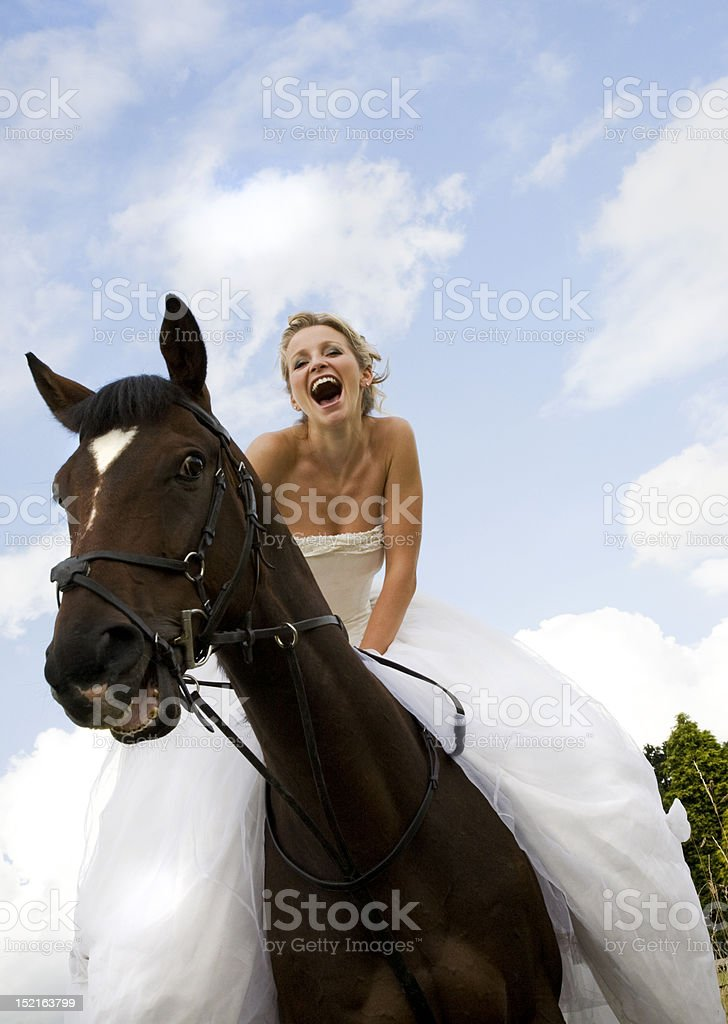 beautiful bride riding horseback, laughing. royalty-free stock photo