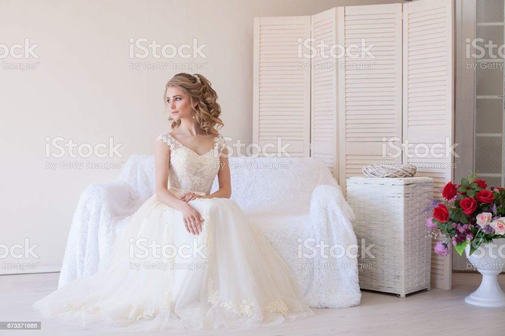 beautiful bride sitting on a white couch in wedding dress stock photo