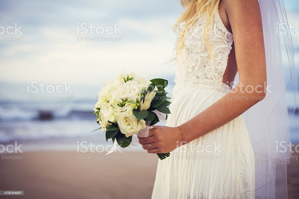 beautiful bride standing by the beach at sunset stock photo
