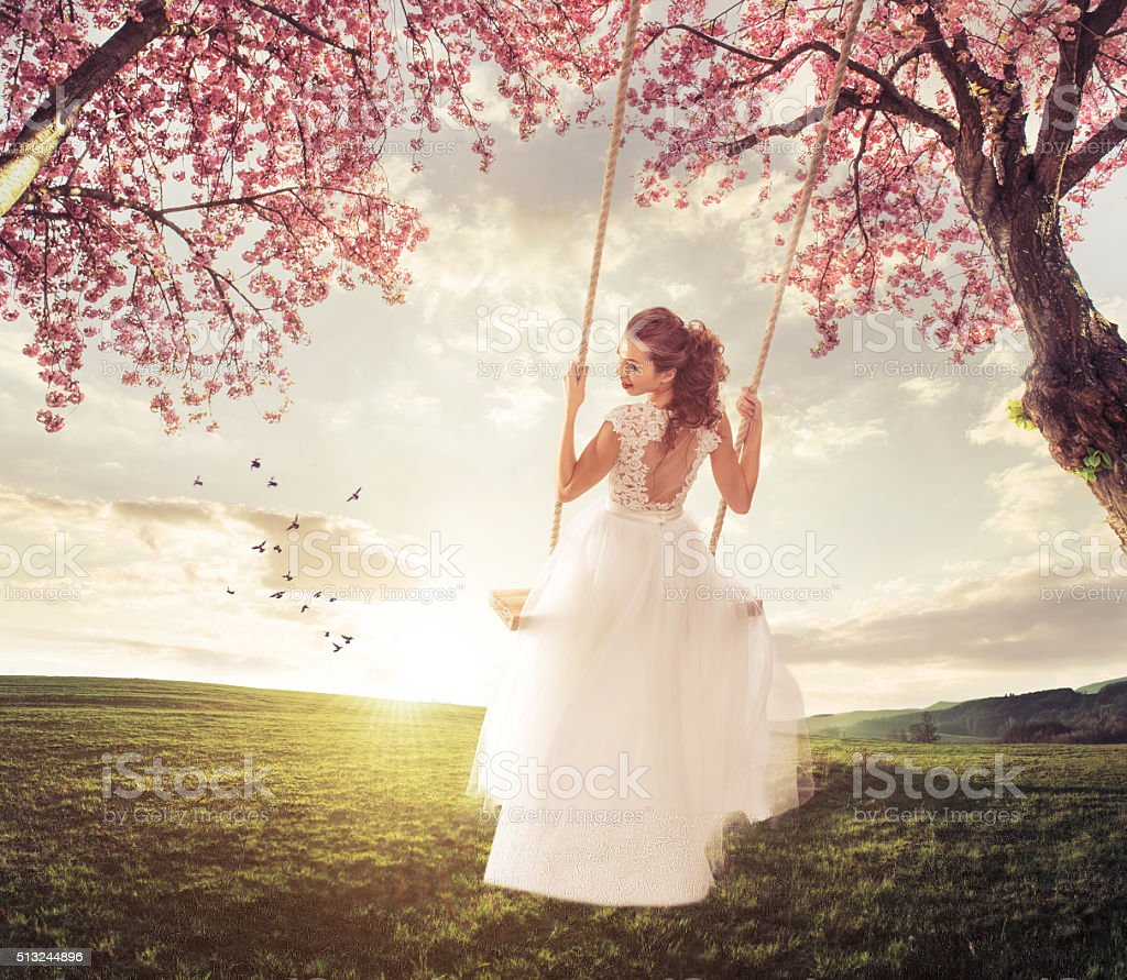 Beautiful Bride swing in the spring meadow stock photo