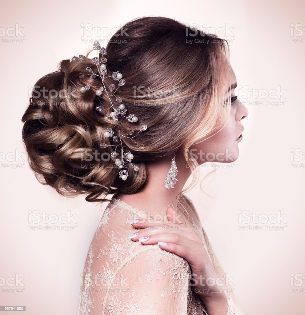 Beautiful bride with fashion wedding hairstyle - on beige background. stock photo