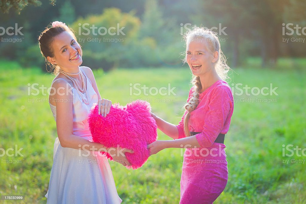 Beautiful bride with her best friend holding furry heart royalty-free stock photo