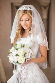 Beautiful bride woman with bouquet of flowers, wedding makeup
