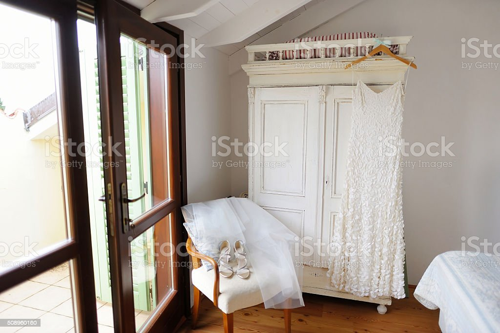 Beautiful bride's dress hanging in white room stock photo