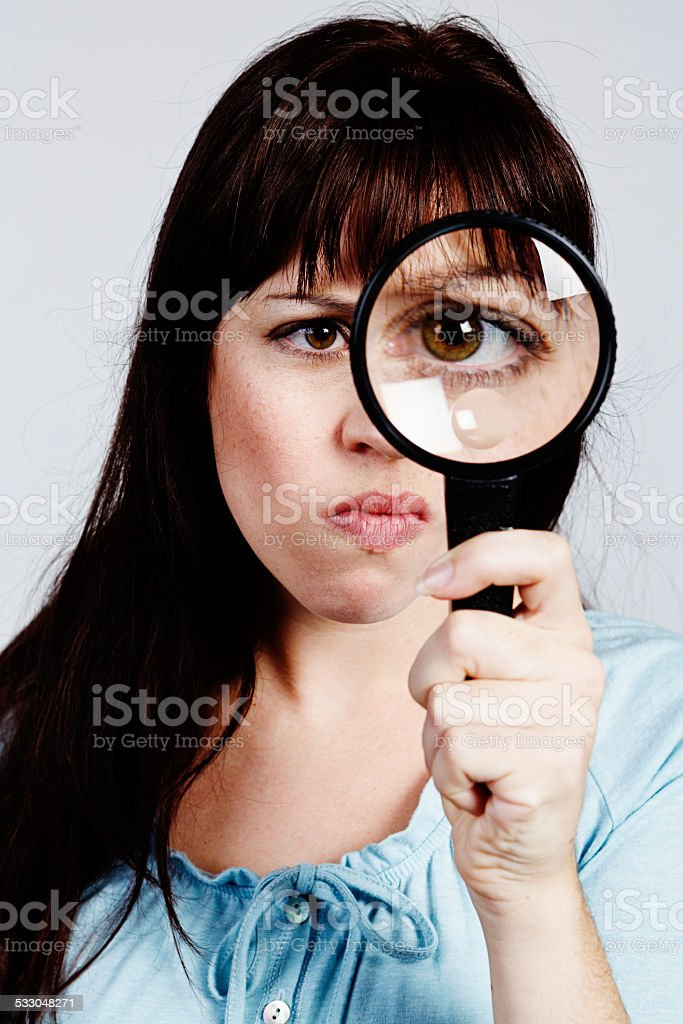Beautiful brown-eyed brunette frowns through magnifying glass stock photo