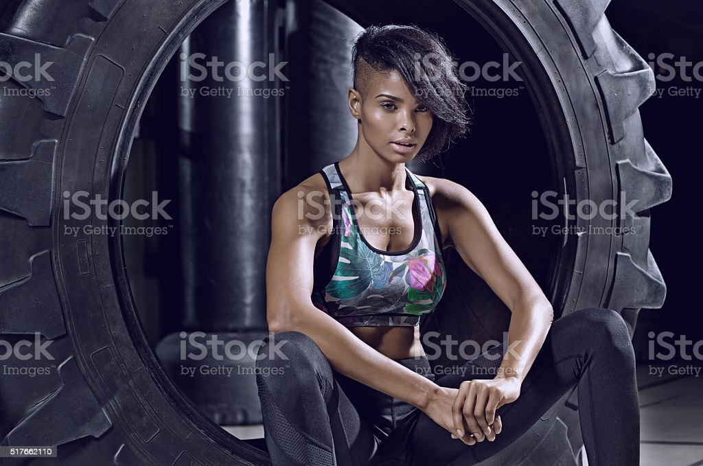 Beautiful brunette athletic woman posing with tyre in a gym stock photo