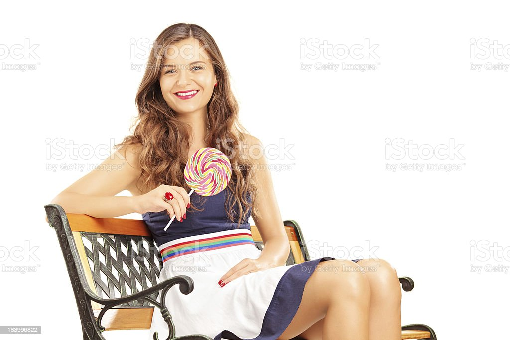 Beautiful brunette female sitting and holding a lollipop royalty-free stock photo