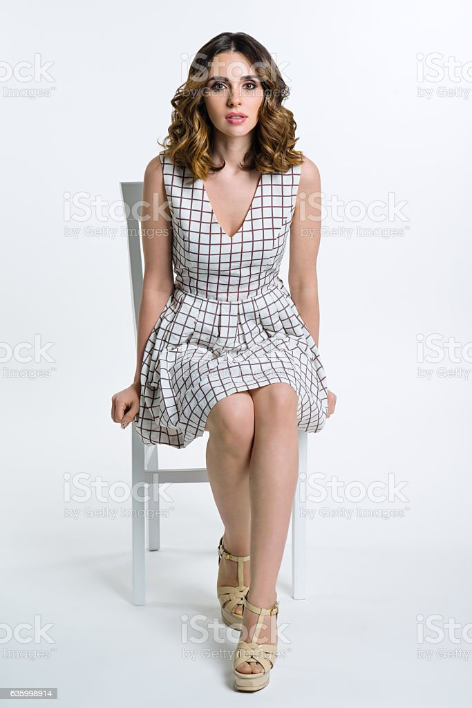 Beautiful brunette girl in checkered dress stock photo