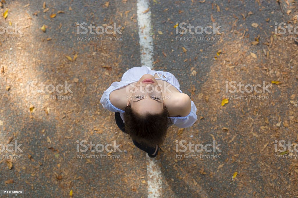 Beautiful brunette girl looking high up. Directly above view. stock photo