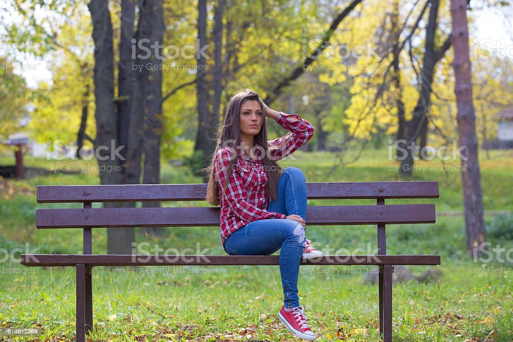 Beautiful brunette girl sitting lonely on park bench stock photo