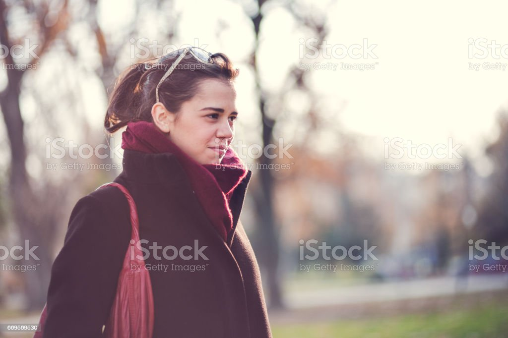Beautiful Brunette Girl Standing At Park On Cold Day stock photo